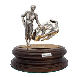 Figura de torero con capote y espada fabricado en plata de primera ley sobre peana de madera - Del siglo XX –